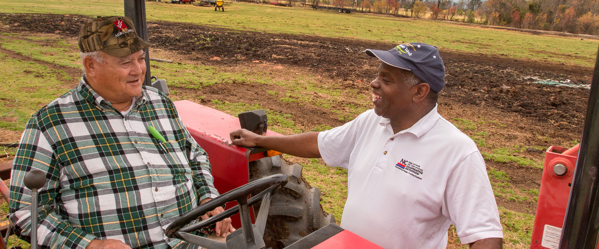 Extension agent talking to small farmer on a tractor