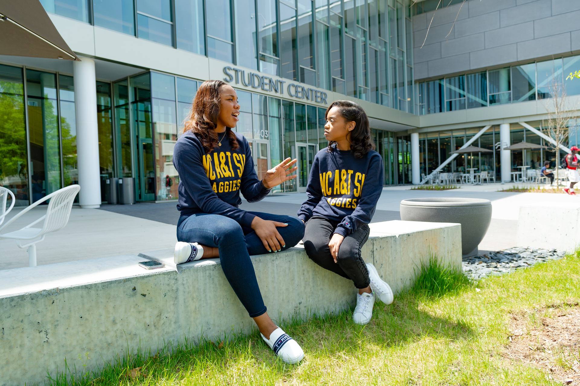 two students wearing NC A&T Aggies shirts sitting in front of the student center